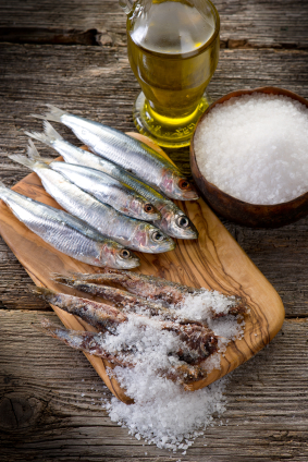Salted herring on a board. A bowl of sea salt and great olive oil makes the dish complete.