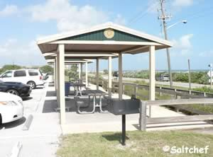 4 small pavilions with grills near parking lot
